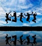 Silhouet van het gelukkige groep mensen springen Stock Foto's