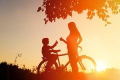 Silhouet van het gelukkige moeder en zoons biking bij zonsondergang stock foto