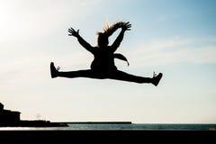 Silhouet van het gezonde jonge meisje springen hoog in lucht in stad met overzees in de zomer in openlucht royalty-vrije stock fotografie