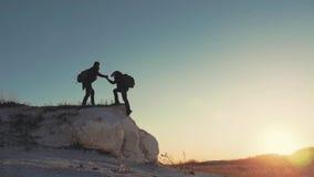Silhouet van het helpen van hand tussen klimmer twee twee wandelaars bovenop de berg, een mens helpt een mens om een zwenking te  stock video