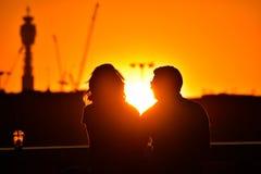 Silhouet van het houden van van paar die op mooie heldere romantische zonsondergang letten royalty-vrije stock afbeelding