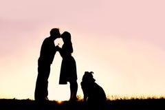 Silhouet van het Houden van het Jonge Paar Kussen buiten op Datum bij Zon Stock Afbeelding