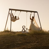 Silhouet van het jonge die paar spelen op schommeling bij zonsondergang wordt geplaatst royalty-vrije stock fotografie