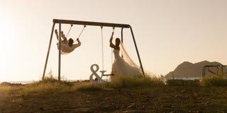 Silhouet van het jonge die paar spelen op schommeling bij zonsondergang wordt geplaatst stock fotografie