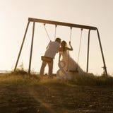 Silhouet van het jonge die paar spelen op schommeling bij zonsondergang wordt geplaatst royalty-vrije stock afbeelding