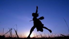 Silhouet van het jonge heks springen op de bezemsteel bij zonsondergang stock video