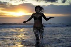 Silhouet van het jonge mooie en sexy Aziatische vrouw vrij en gelukkig lopen hebbend pret bij zonsondergangstrand in Bali stock afbeelding