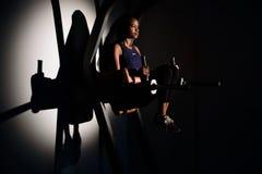 Silhouet van het jonge schitterende Afrikaans-Amerikaanse de instructeur van de vrouwengeschiktheid uitwerken bij de gymnastiek stock afbeeldingen