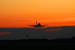 Silhouet van het landende vliegtuig op een zonsondergang. Stock Foto