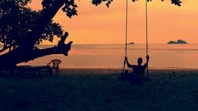 Silhouet van het mooie meisje ontspannen op een schommeling bij het strand stock videobeelden