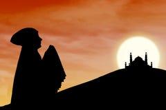 Silhouet van het moslimvrouw bidden dichtbij moskee Stock Foto's