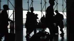 Silhouet van het overgaan van mensen in luchthaventerminal stock videobeelden