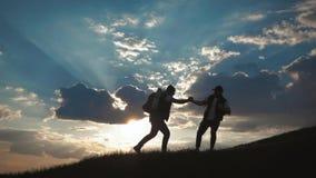 Silhouet van het team op de piek van berg Sport en het actieve leven van mensen tweepersoons De hulp van het groepswerkpaar stock videobeelden