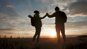 Silhouet van het team op de piek van berg Sport en het actieve leven van de mensenmens en meisje De hulp van het groepswerkpaar stock videobeelden
