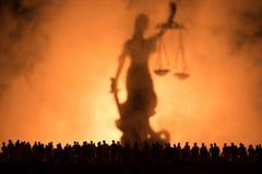 Silhouet van het vage reuzestandbeeld van de damerechtvaardigheid met zwaard en schaal die zich achter menigte bij nacht met mist stock foto's