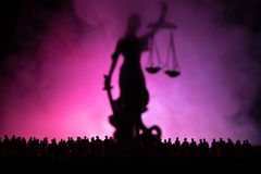 Silhouet van het vage reuzestandbeeld van de damerechtvaardigheid met zwaard en schaal die zich achter menigte bij nacht met mist royalty-vrije stock foto's