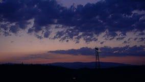 Silhouet van Hoogspannings elektrische pyloon, toren in zonsondergang stock footage