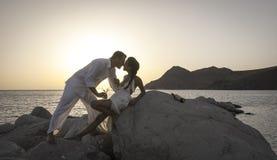 Silhouet van jong gelukkig paar die pret op strandrotsen hebben bij zonsopgang royalty-vrije stock foto's