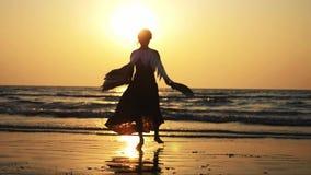Silhouet van jong meisje met vleugels die bij zonsondergang in langzame motie dansen stock video
