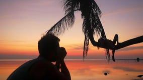 Silhouet van jong paar op het strand De mens neemt een beeld zijn meisje terwijl het meisje op een palm tijdens ligt stock footage