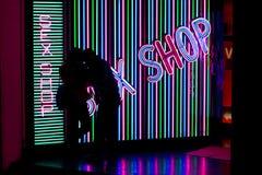 Silhouet van jong paar tegen geslachtswinkel Stock Afbeeldingen