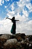 Silhouet van jonge aantrekkelijke vrouw met geopende wapens in openlucht i Stock Fotografie