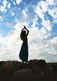 Silhouet van jonge aantrekkelijke vrouw met geopende wapens in openlucht i Stock Afbeeldingen
