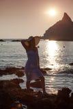 Silhouet van jonge dame door de oceaan met bergen op backgrou Royalty-vrije Stock Afbeelding