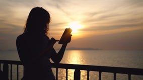 Silhouet van jonge donkerbruine vrouw in zonnebril die zich op dek van cruiseschip bevinden en haar slimme telefoon met behulp va stock videobeelden