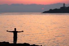 Silhouet van jonge mensen met open wapens op het overzees Royalty-vrije Stock Foto's