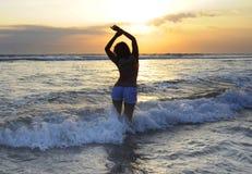 Silhouet van jonge mooie Aziatische vrouw status bij water het vrije en ontspannen bekijken horizon op zonsondergangstrand in Bal stock foto