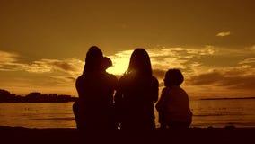 Silhouet van jonge ouders met twee jonge geitjes die op de zonsondergang op het strand letten Mensen die pret op het overzees heb stock video
