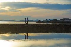 Silhouet van jonge romantische paar holding en het spelen van met zoon of dochter weinig baby die van zonsondergang genieten die  stock foto