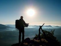 Silhouet van jonge toeristengids die in document kaart kijkt royalty-vrije stock afbeelding