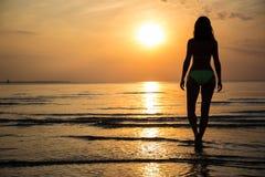 Silhouet van jonge vrouw in bikini die op strand bij zonsondergang lopen Stock Foto's