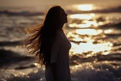 Silhouet van Jonge Vrouw het Letten op Overzeese Zonsondergang Meisje met lange krullende rode haar enjoing zon royalty-vrije stock afbeelding