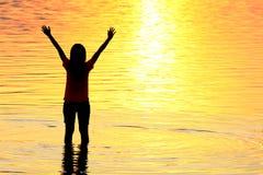 Silhouet van jonge vrouw tegen de zomerzonsondergang Royalty-vrije Stock Afbeelding