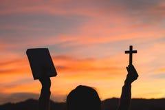 Silhouet van Jonge vrouwenhanden heilige Bijbel en lift van christelijk kruis houden, godsdienstsymbool in licht en landschap die royalty-vrije stock foto's