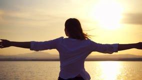 Silhouet van jonge vrouwenrotatie bij zonsondergang op meer Vrouwelijke cijferdans bij gouden uur in langzame motie stock video