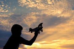 Silhouet van jongen die houten vliegtuig in aard spelen royalty-vrije stock foto