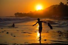 Silhouet van jongen het lopen langs de zonnestraal van de strandzonsondergang Royalty-vrije Stock Afbeeldingen