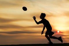 Silhouet van jongen het spelen bal bij zonsondergang Royalty-vrije Stock Afbeeldingen