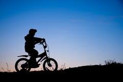 Silhouet van jongen op fiets royalty-vrije stock foto's