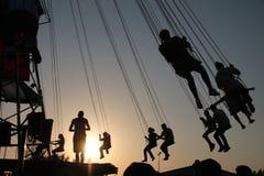 Silhouet van jongeren op Reuzenrad en slingerende carrousel in eindemotie op zonsondergangachtergrond stock foto's