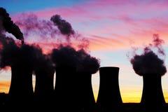 Silhouet van kernenergieinstallatie tijdens zonsondergang Stock Foto's