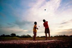 Silhouet van kinderen die document vliegtuig spelen bij zonsondergang Royalty-vrije Stock Foto