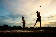Silhouet van kinderen die document vliegtuig spelen bij zonsondergang Stock Foto's