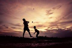 Silhouet van kinderen die document vliegtuig spelen bij zonsondergang Royalty-vrije Stock Fotografie