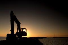 Silhouet van lader voor graafmachines bij het zonsondergangstrand erachter royalty-vrije stock fotografie