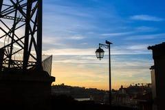 Silhouet van lamp met vogel op achtergrond van de stad en de schemering blauwe hemel Wolken Stock Foto's